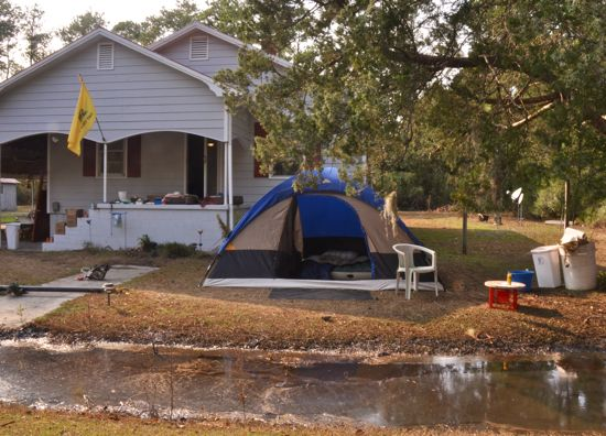 A tent and mattress inside set up in front of one home in Lowland. The water in the foreground is a drainage ditch and was filled because the water levels ... & Irene at Hobucken and Lowland