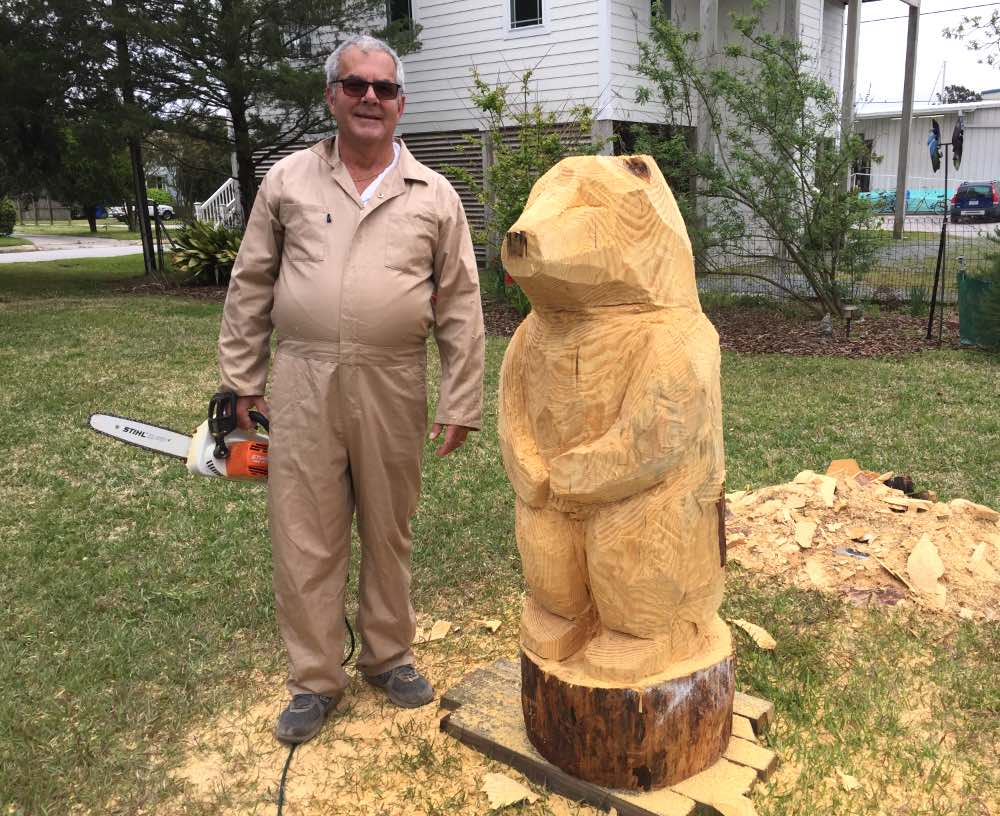 A man in coveralls holds a chainsaw. Next to him is a half-carved tree stump the height of his shoulder. A rough bear shape is carved into the stump.