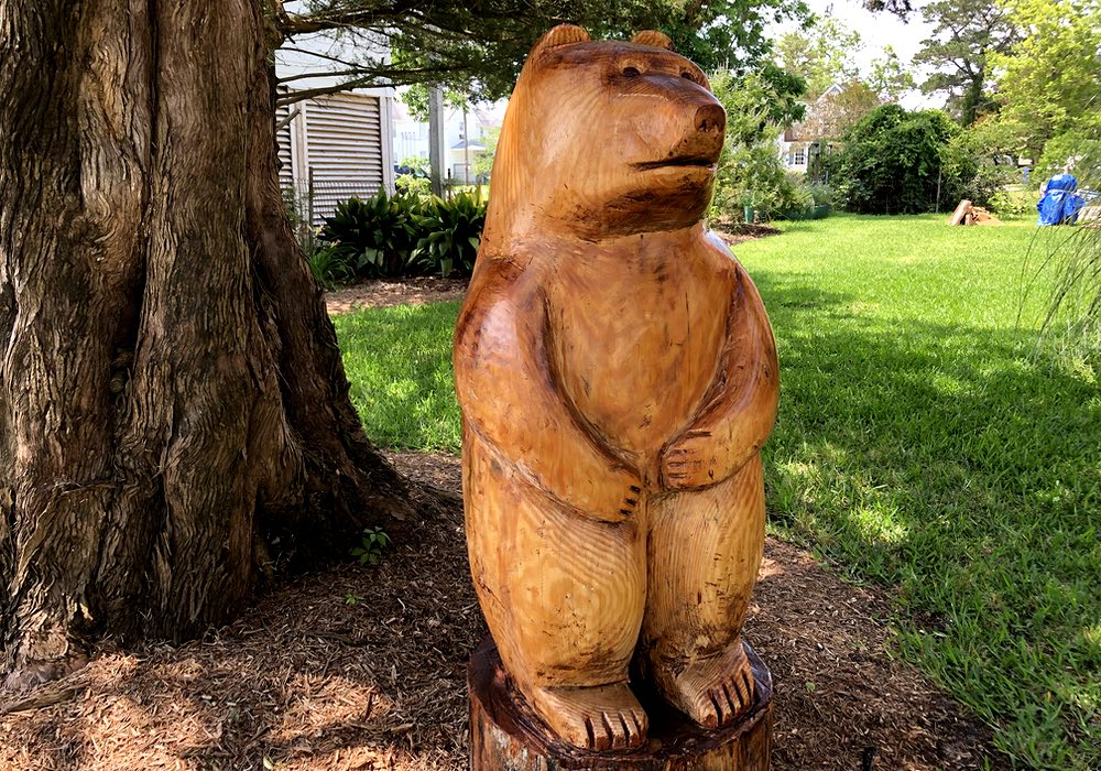 The finished bear carving stands upright on a stump, two paws close to the front of its body, looking straight out at the street.