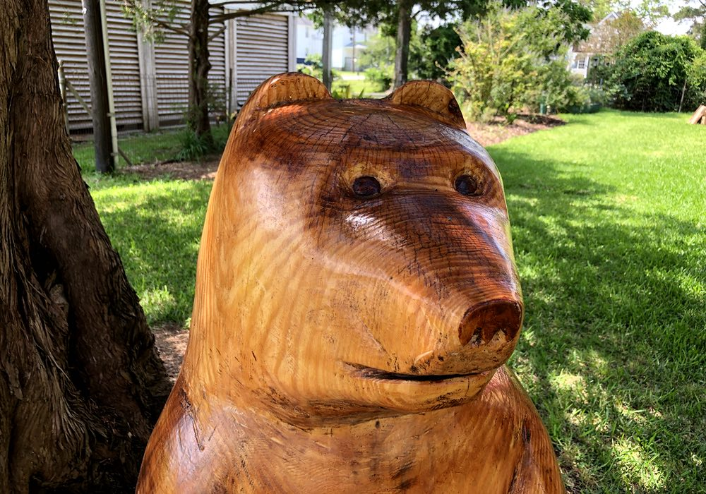Close-up picture of a carved bear's head and shoulders. The wooden bear is stained and sealed against the weather.