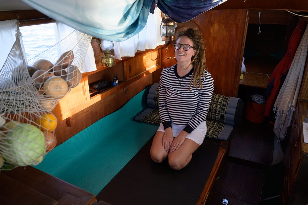 Inside the cabin, Emily kneels on yoga mats are laid out on top of the berth. Netting hangs from the ceiling, holding fresh produce.