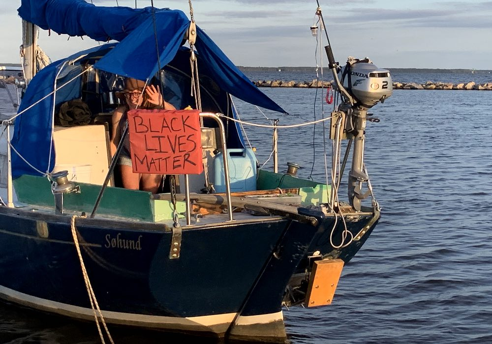 A Black Lives Matter sign on the stern of a blue boat called Søhund. Emily smiles and waves from the companionway.