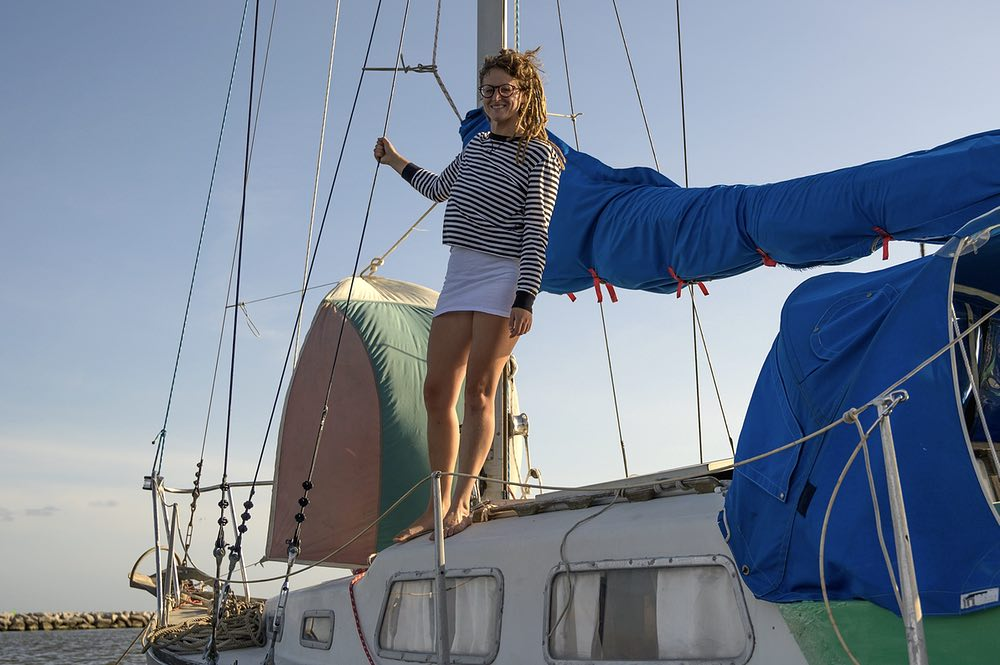 A blond woman with dreadlocks and wearing glasses stands on the deck of her sailboat