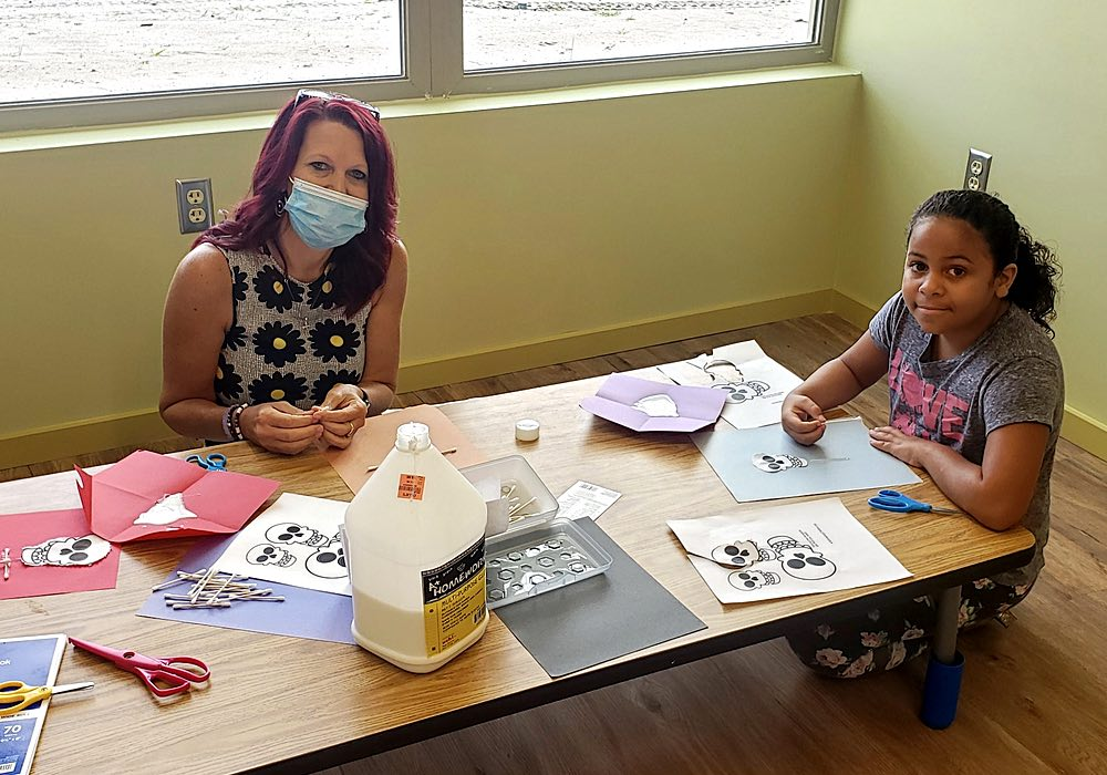 A masked teacher and a student work on an art project.