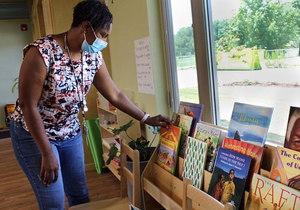 The program director wears a mask as she arranges children's books on a wooden bookshelf.