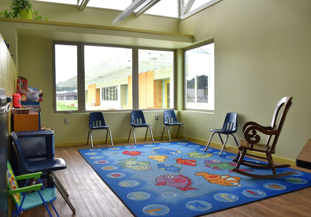 A brightly colored rug sits in a corner. Windows are on both walls.