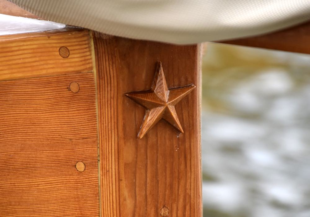 A small, wooden, five point star decorates the bow of the boat.