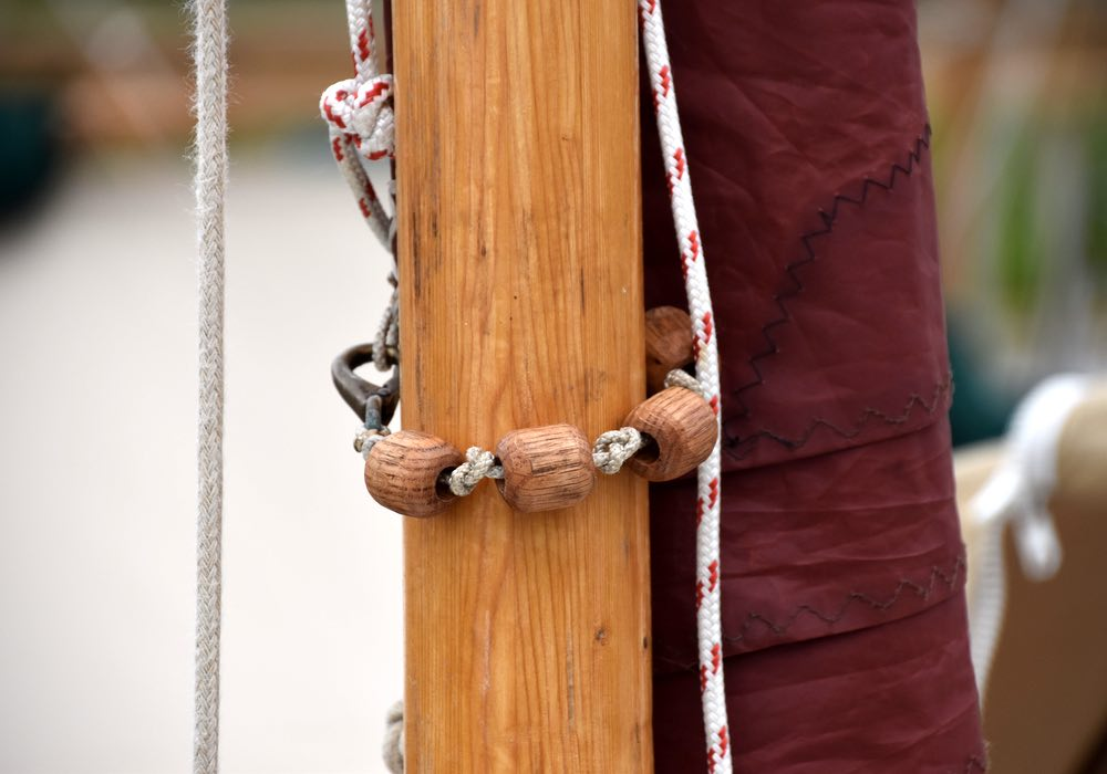 Wooden beads cover the sail line and wrap around the mast to keep the line from rubbing.