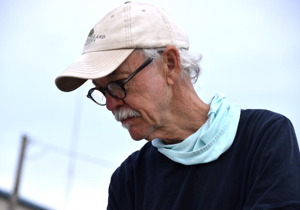 A close-up of Curt, wearing a white hat, light blue neck gaiter, and glasses as he looks down into a boat.