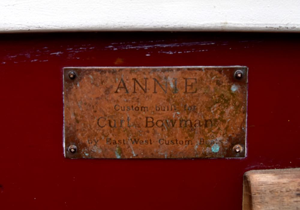 A close-up of a weathered plaque says ANNIE Custom Built for Curt Bowman by East West Custom Boats.