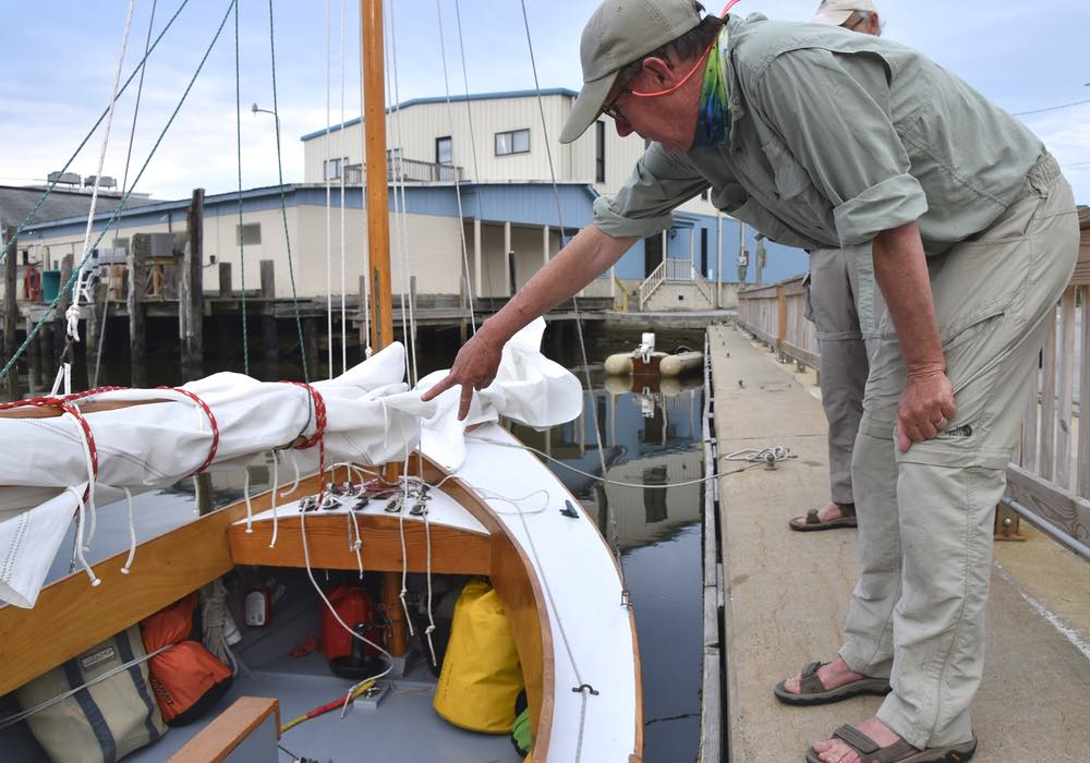 Steve stands on the bulkhead, leaning over a boat in the water, pointing to a equipment stowed under the gunwale.