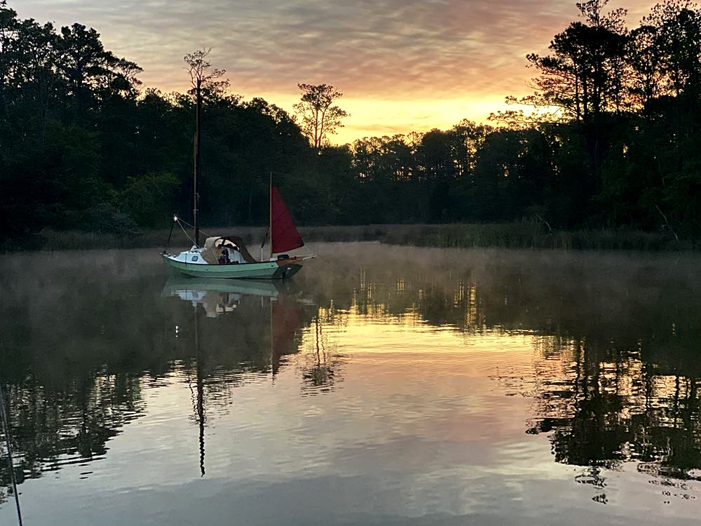 A small sailboat is anchored in the water. It's sunrise. There are trees on the bank and fog on the water.