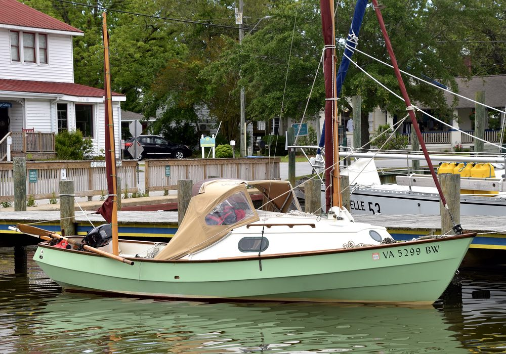 A small green sail boat alongside a dock.