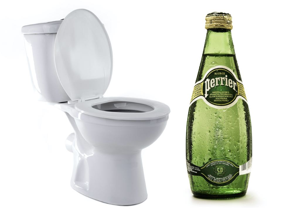 A toilet next to a bottle of Perrier water.