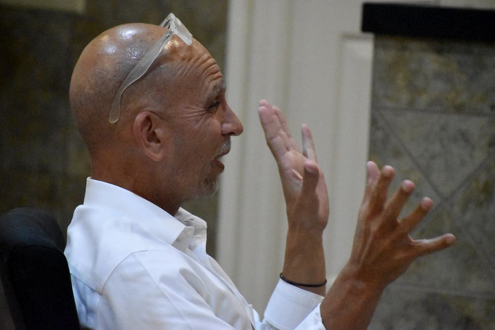 A bald man wearing a white shirt and with glasses pushed onto his head gestures with his hands while he speaks.