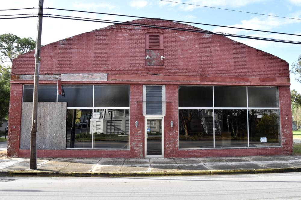 An abandoned red brick building on a street corner. One front window is boarded over with a sheet of plywood.