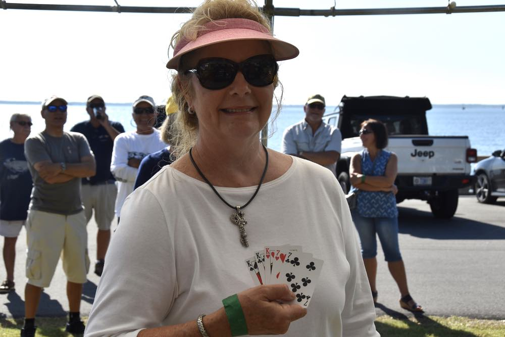 A blonde woman in glasses and sun visor holds 5 cards showing a winning poker hand.