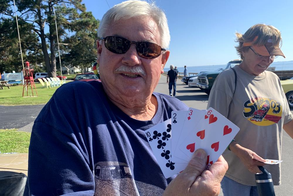 An older man with white hair, wearing sunglasses and a purple shirt, displays his incomplete, but losing hand: a 10, a 2, a 3, and a 6.
