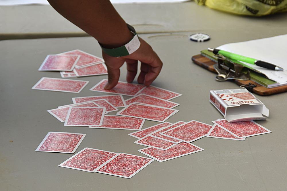 Several red cards are face down on a table. A hand reaches into the frame to pick one up.