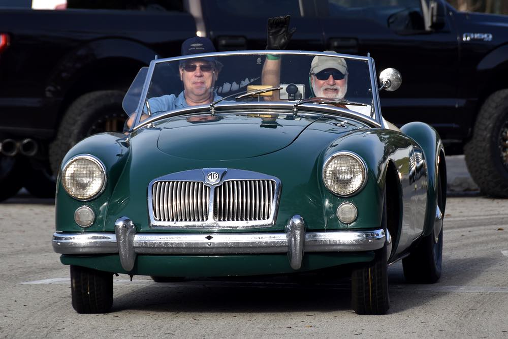 Two men ride in a green vehicle. The top is down and the driver waves a black-gloved hand at the camera.