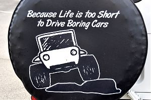 A black spare tire cover with a hand-drawn depiction of a jeep riding over rocks. It says, 'Life is too short to drive boring cars'