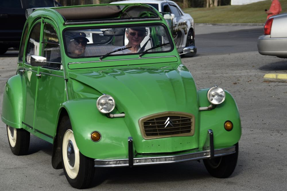 Front view of a green Citroen, with driver and passenger.