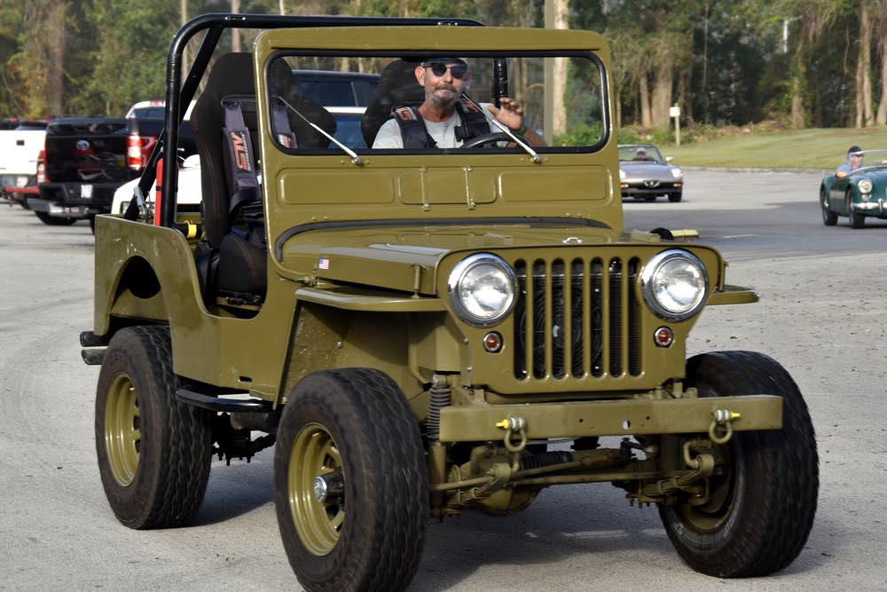 A man in a baseball hat and wearing a four point harness seat belt drives an olive drab green jeep with open top and sides.