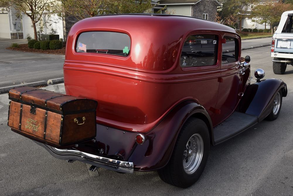 A wooden trunk with the word FORD on it rides over the back chrome bumper of an antique red and black Ford coupe.