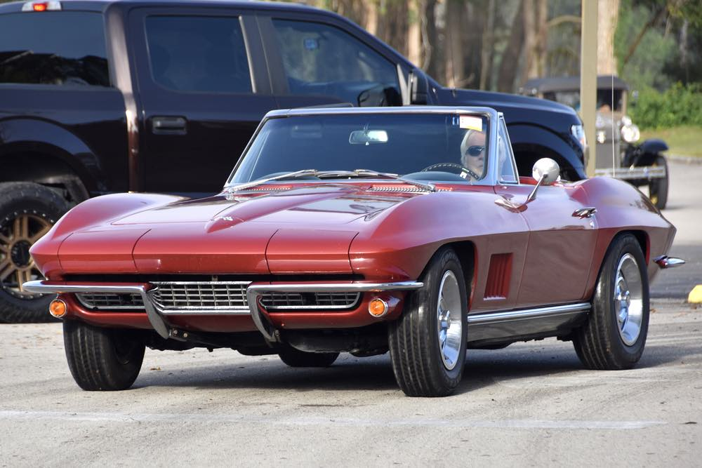 A white haired man drives a red corvette.