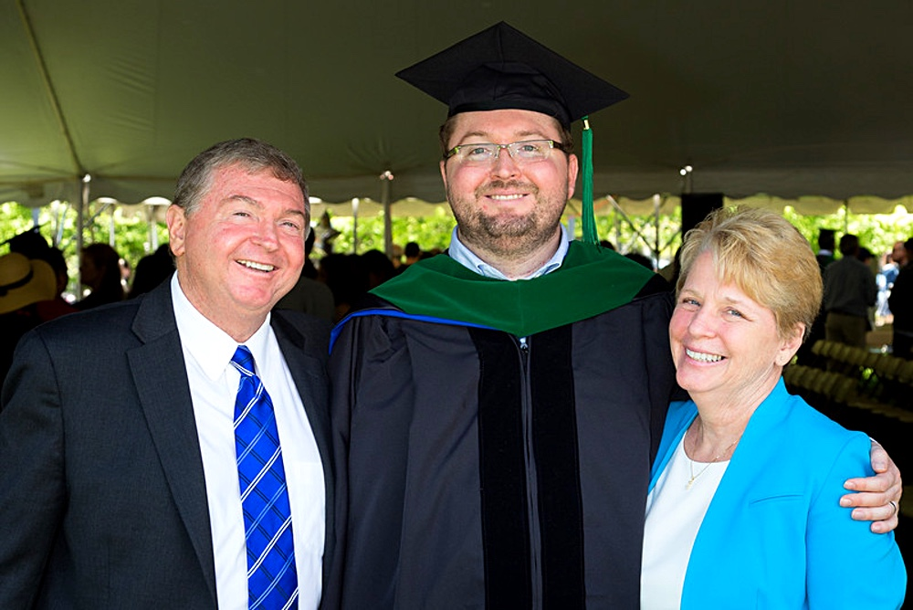 A tall man wearing a black graduation hat stands between a shorter couple. The couple half embrace the younger man as all smile at the camera.