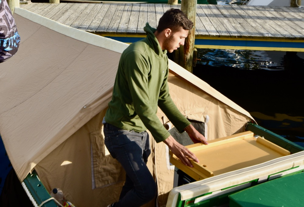 Evan stands in the boat, in front of a canvas cover fastened to the boat over an a-frame.