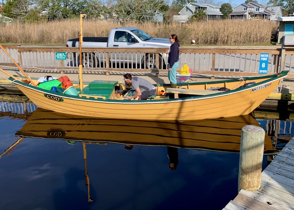 Side view of the Dory <em>Cod</em> from the town dock. Ariana stands on the sea wall and Evan is busy moving gear in the boat.