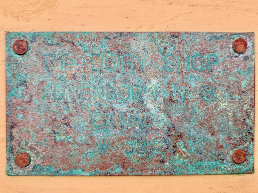 a blue patina covered plaque held to the boat with four rust colored screws in the corners.