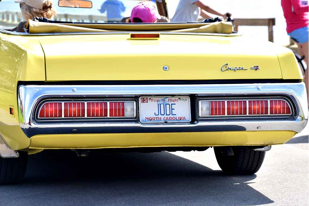 The back end of a yellow 1973 Mercury Cougar with chrome and red taillights and a license plate that reads JUDE.