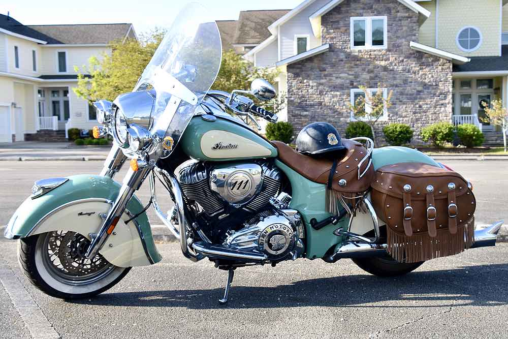 An aqua-green and cream colored motorcycle sits in a parking lot. A black helmet rests on the brown leather seat. Brown leather fringe decorates it and the leather saddle bags.