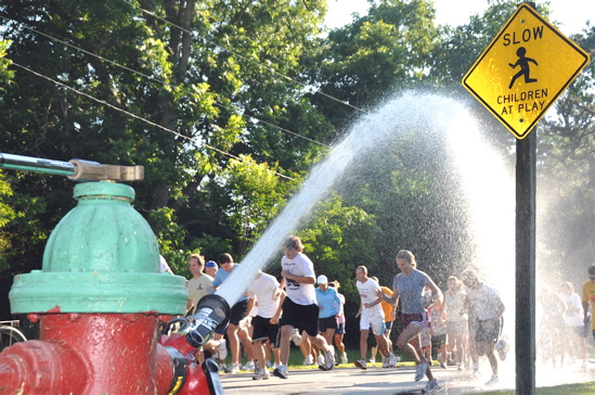 An open fire hydrant cools the crowd during the 2009 Croaker Relay.